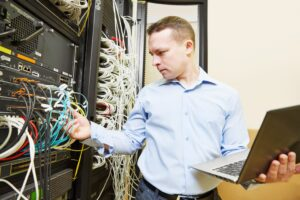 Man working in a server room looking at wires