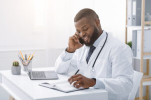 Young doctor talking to patient on phone while working in modern clinic, high quality service concept